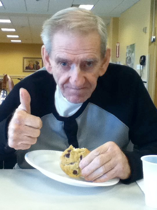 man hiving a thumbs up for a cookie he is eating.